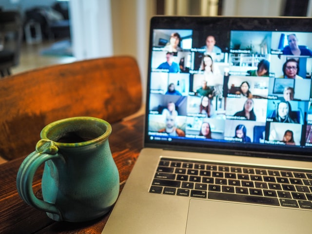 Picture of laptop showing Zoom on screen with a mug next to the laptop