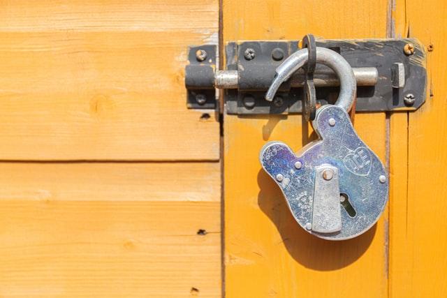 Picture of an unlocked (open) padlock on a door